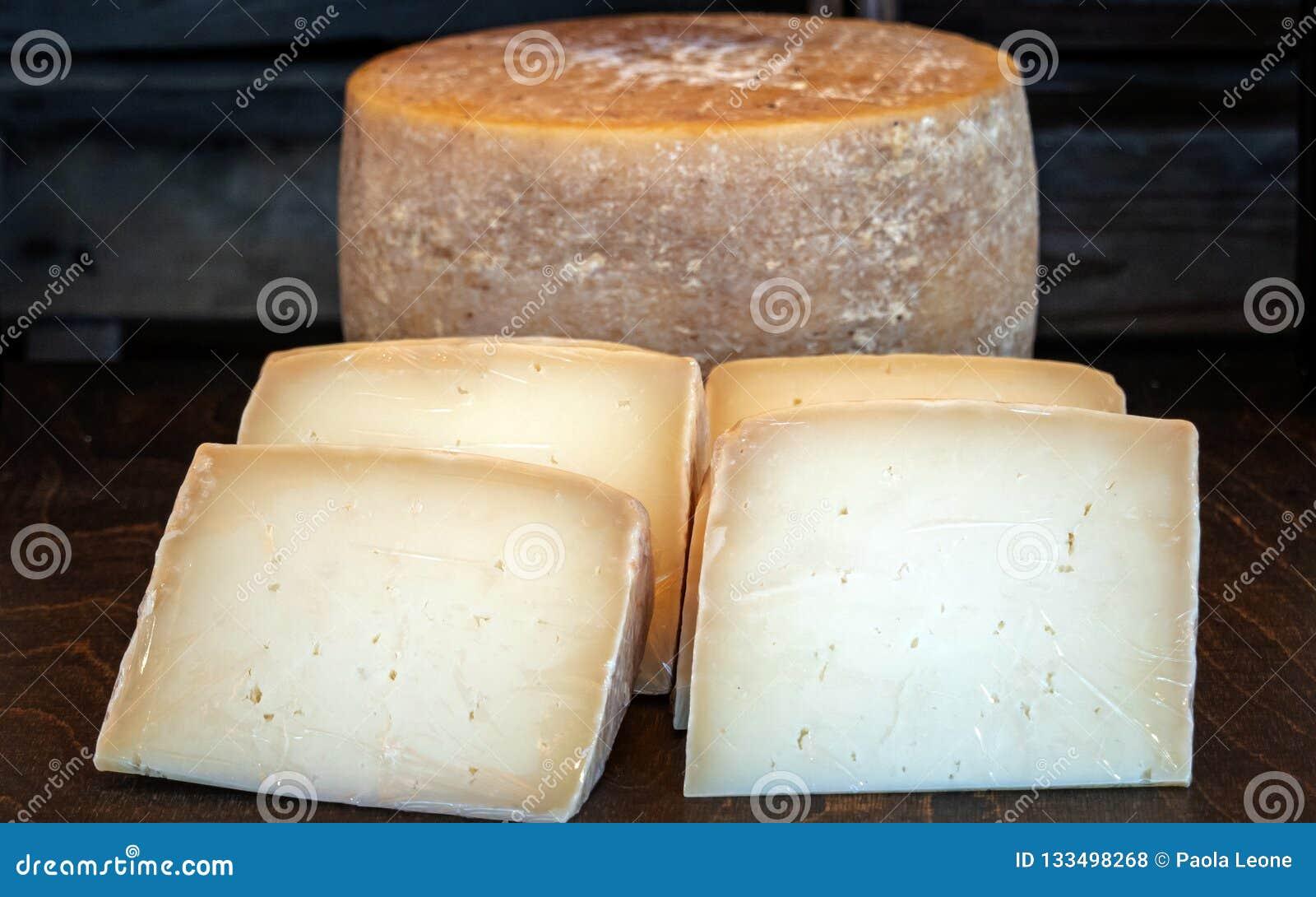 Rueda sana deliciosa fresca del queso, con cuatro rebanadas del queso en primero plano