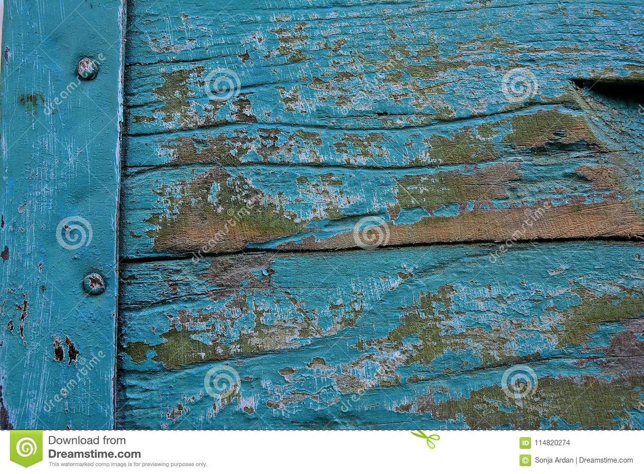 old blue paint and a metal compound of two wooden boards close ap