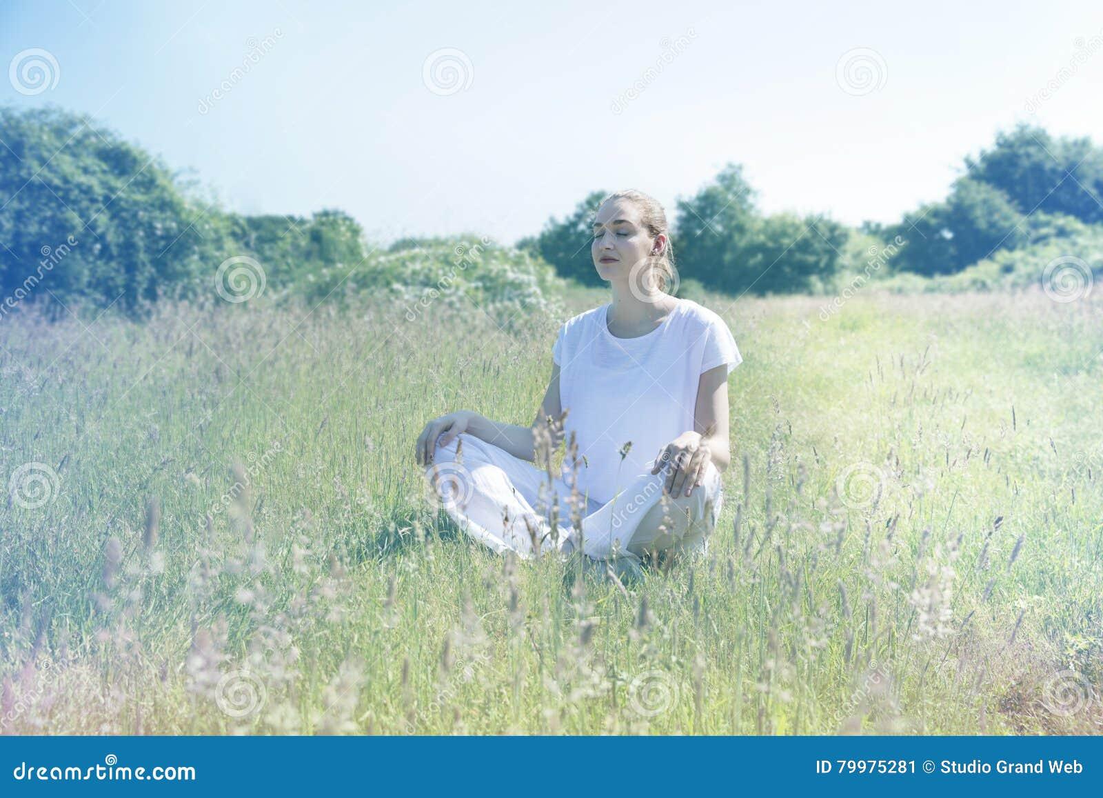 Ruhige junge Yogafrau mit Augen schloss für zentrierten Mindfulness