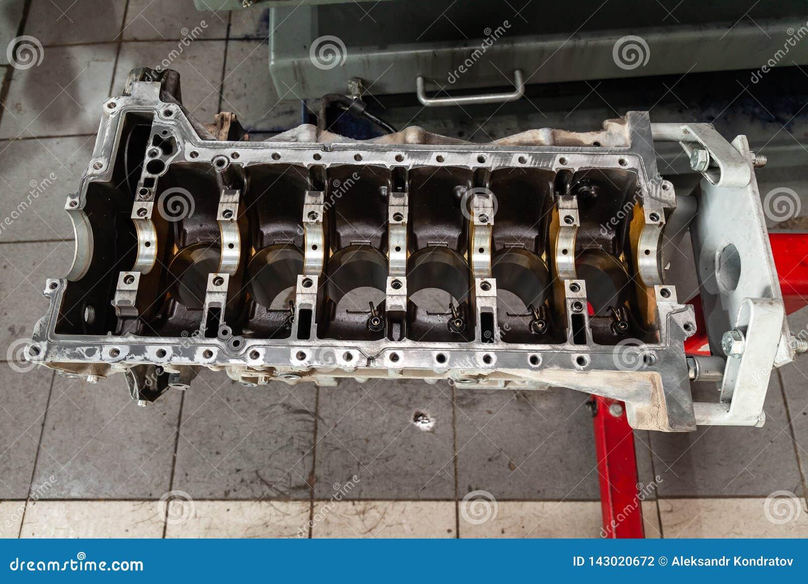 Ruilmotor op een kraan opgezet voor installatie op een auto na een analyse en een reparatie in een workshop van de autoreparatie