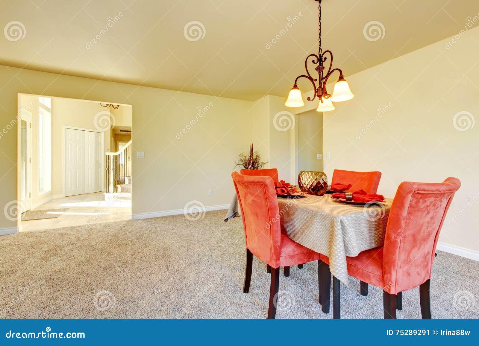 Ruim romig tonenbinnenland van eetkamer met rode stoelen stock
