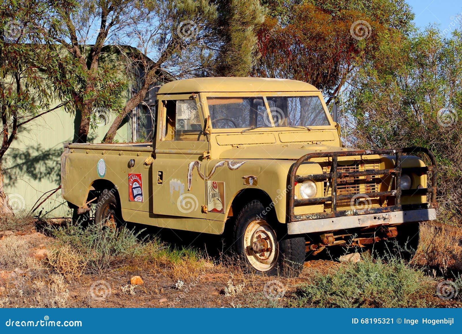 Ruina oxidada del coche de la recogida con las etiquetas engomadas de la cerveza de Carlton Mid, Australia