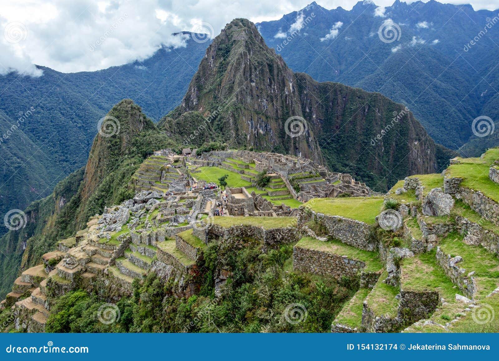 Ruinas abandonadas de la ciudadela Incan de Machu Picchu, del laberinto de terrazas y de las paredes que suben de la maleza grues