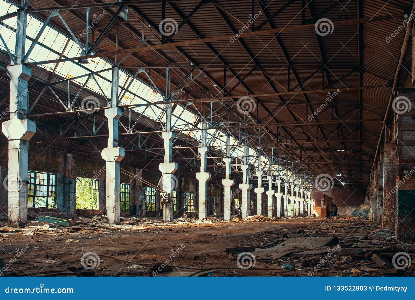 Ruinas de la fábrica o del almacén abandonada con las columnas, la constricción industrial espeluznante y vacía grande