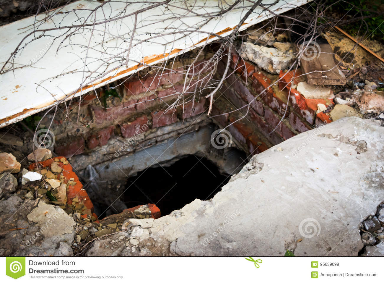 Ruins of destroyed house. Abandoned earthen cellar.