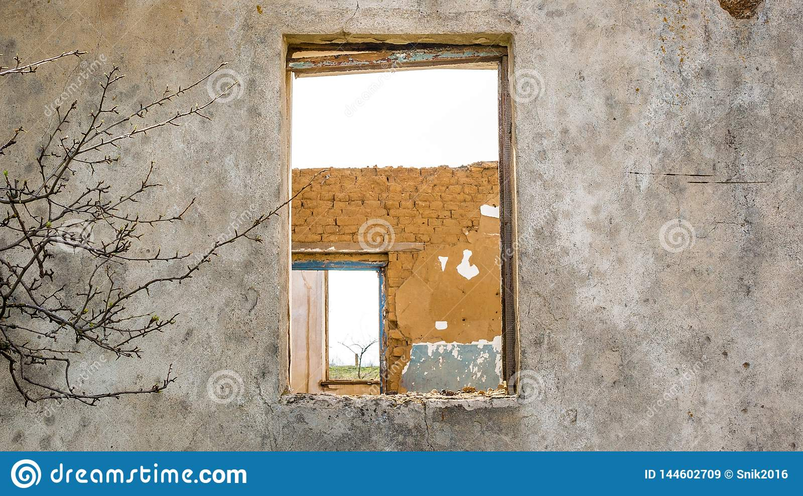 The ruins of an old earthen house without a roof. Holes in the wall at the site of windows and doors