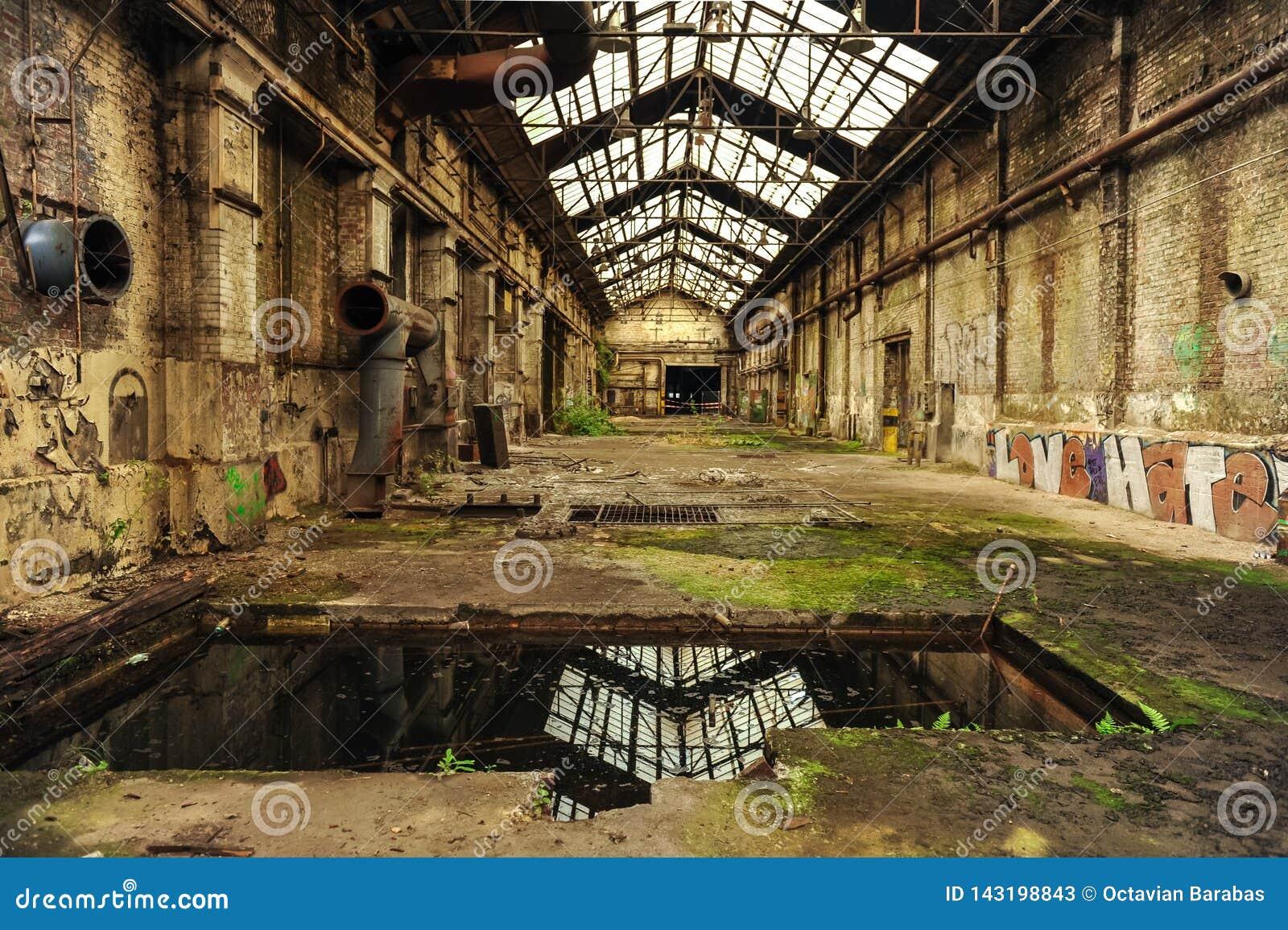 Ruiny fabryczny budynek z roślinnością bierze z powrotem