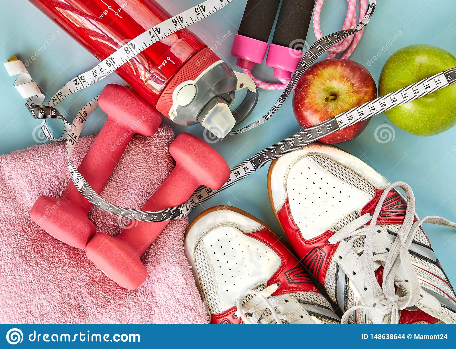 ruits, dumbbells, water bottle, rope, sneakers and meter on a blue background