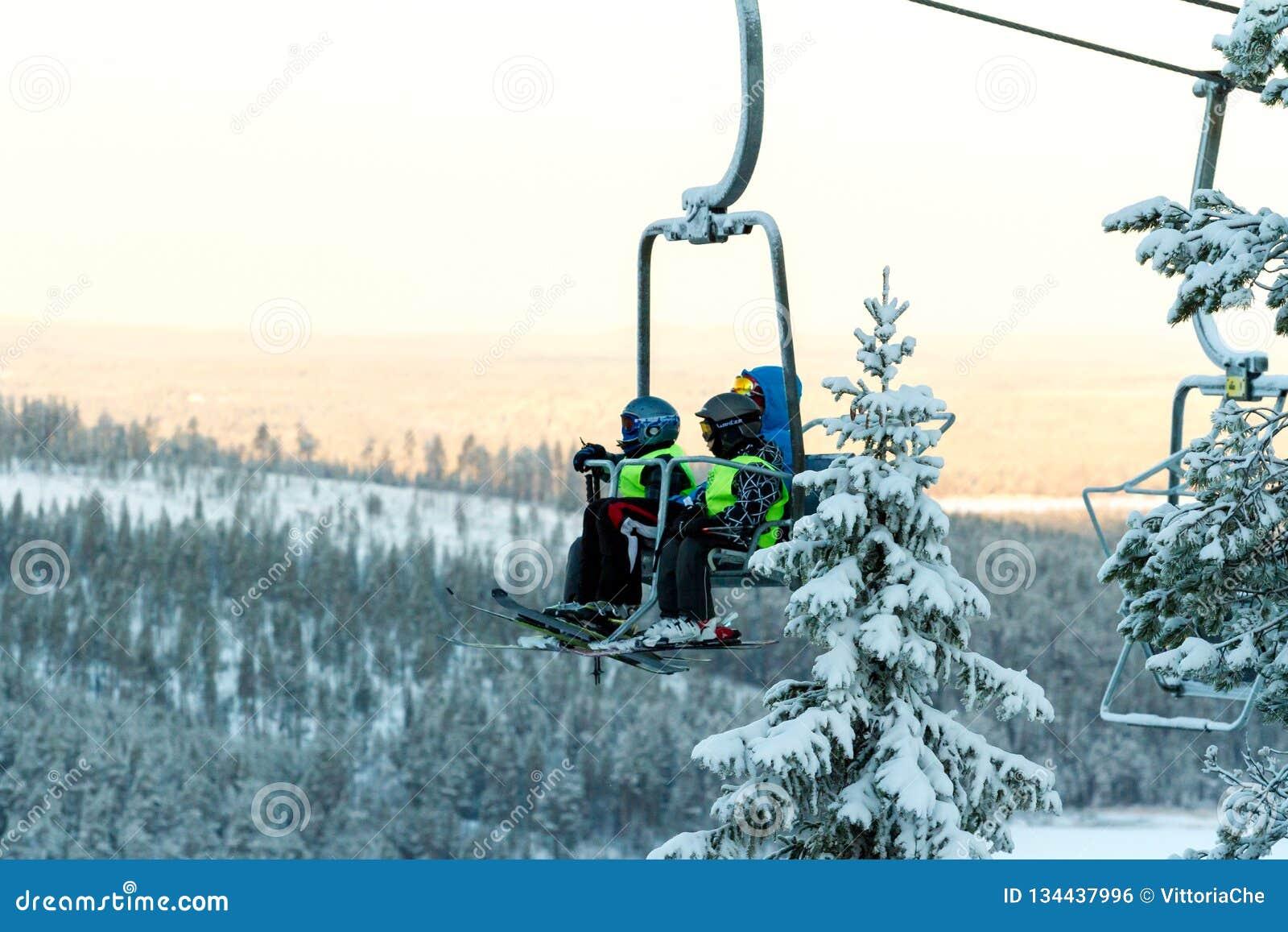 Ruka, Φινλανδία - 27 Νοεμβρίου 2012: Οι σκιέρ κάθονται στον ανελκυστήρα καρεκλών στο χιονοδρομικό κέντρο Ruka στο πάγωμα της ημέρ