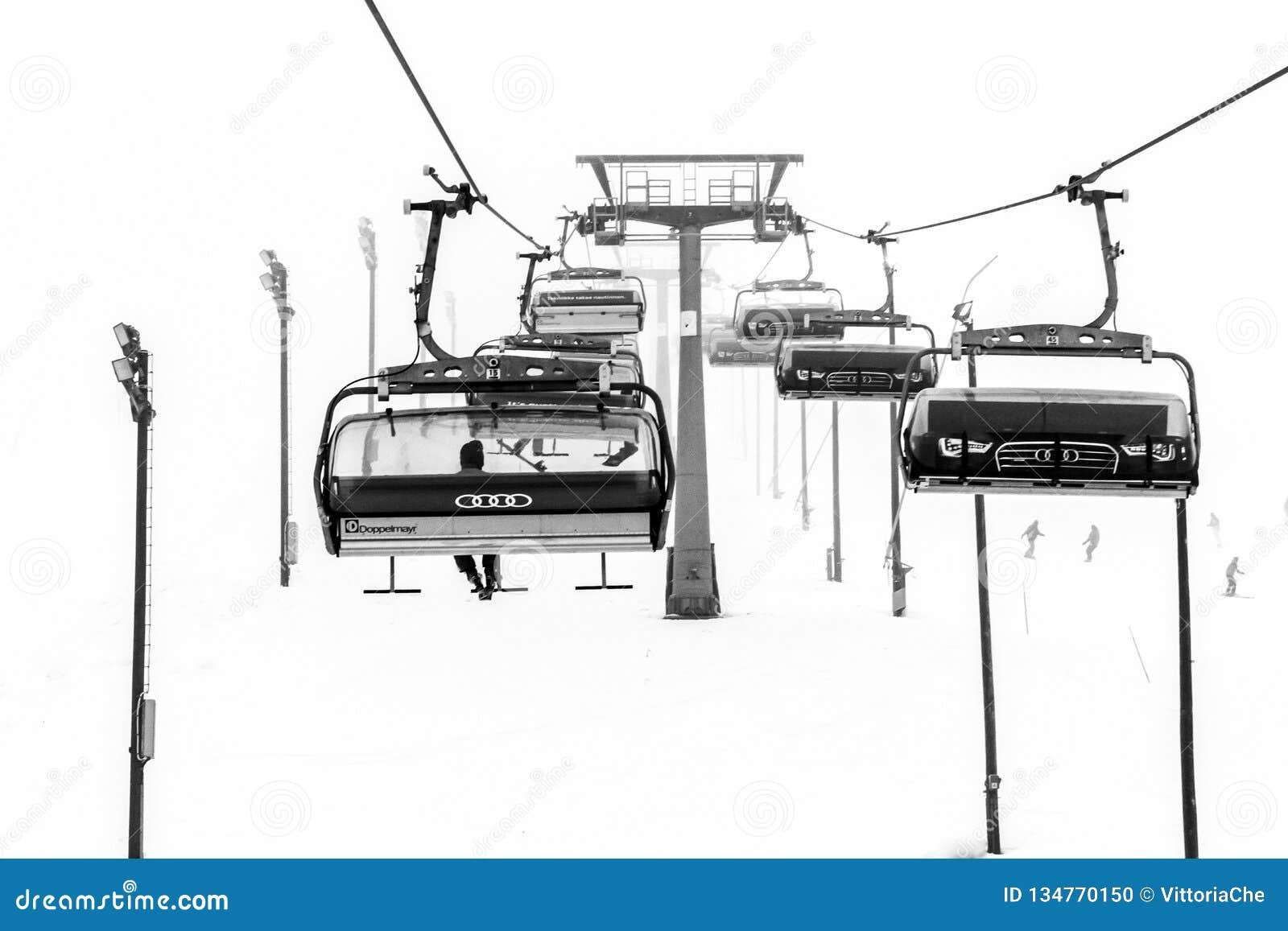 Ruka, Finnland - 24. November 2012: Skifahrer sitzen auf dem Stuhlskiaufzug an Ruka-Skiort an einfrierendem Tag