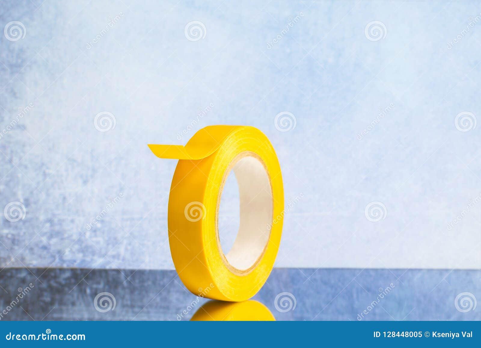 Rulla det gula elektriska bandet på en grå bakgrund