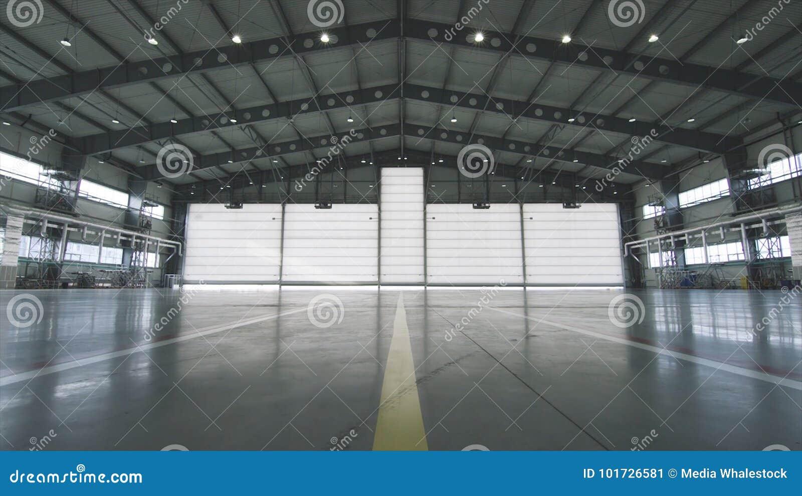 Rullslutaredörr och inre fabriksbyggnad för konkret golv för industriell bakgrund Flygplan framme av halvan