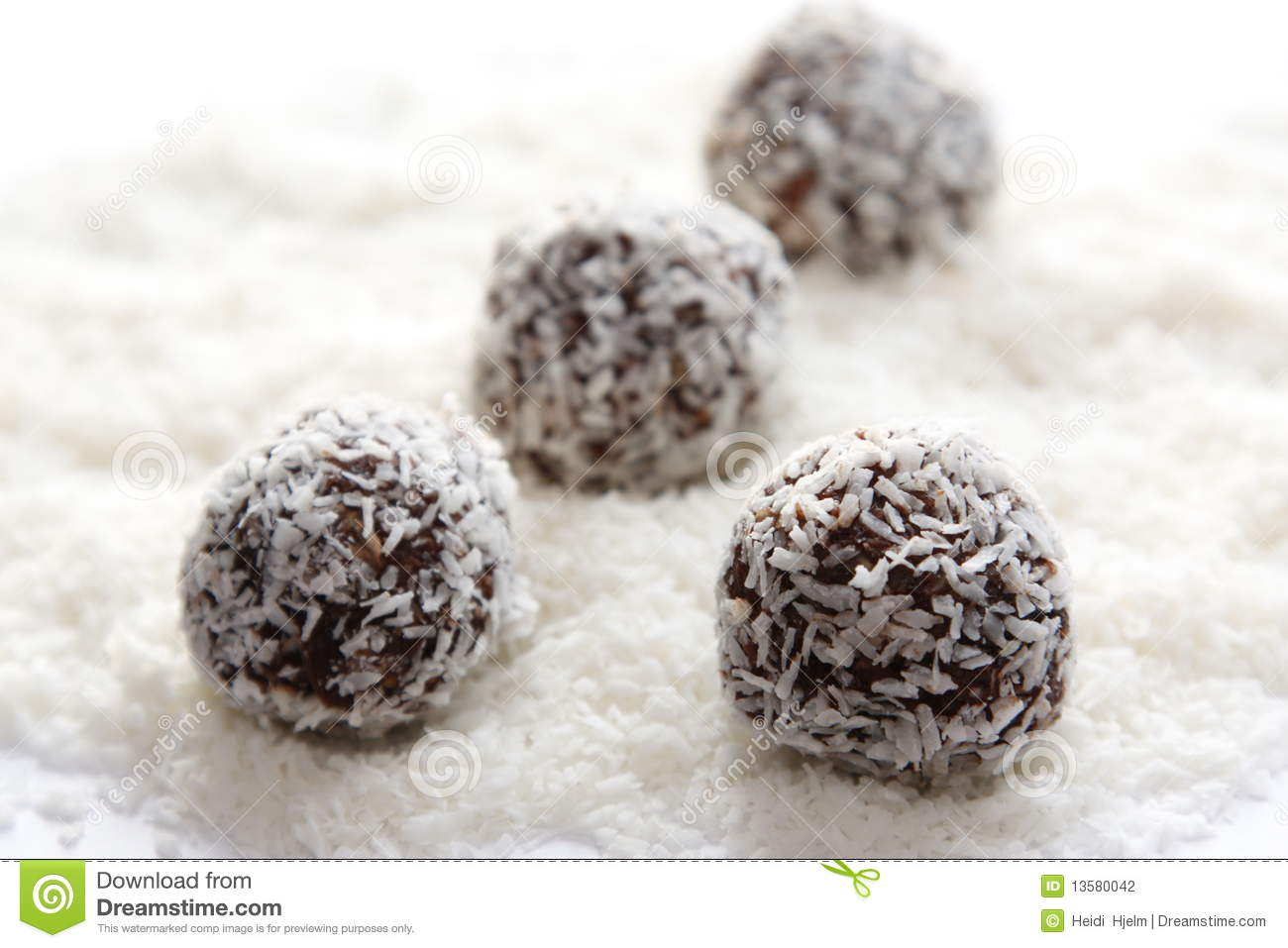 Rum balls on a white background, with coconut powder underneath ...