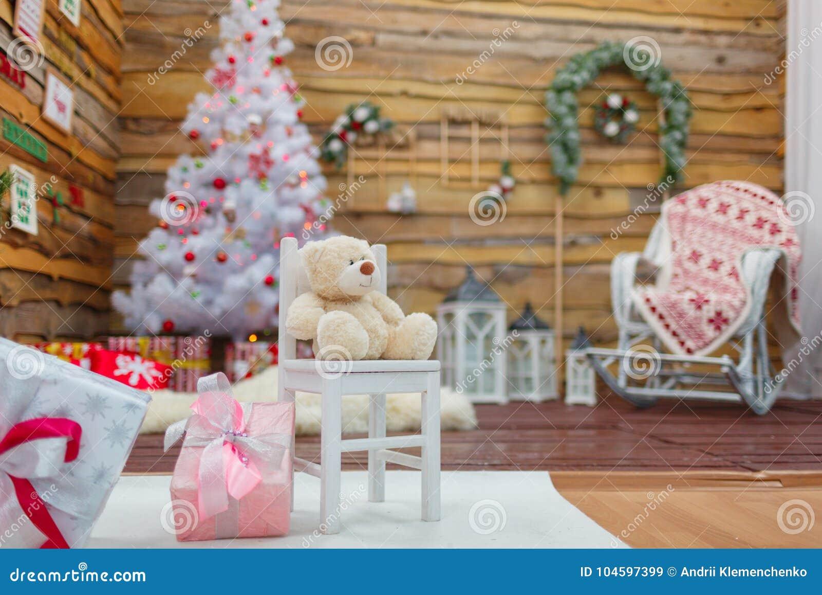 Rummet dekoreras med sörjer filialer och julgranen En nallebjörn sitter på en stol i mitt av rummet