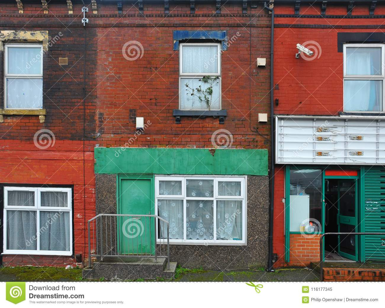 Run down terraced houses on a street in leeds with shabby decaying colourful painted walls and a shop front with an open door