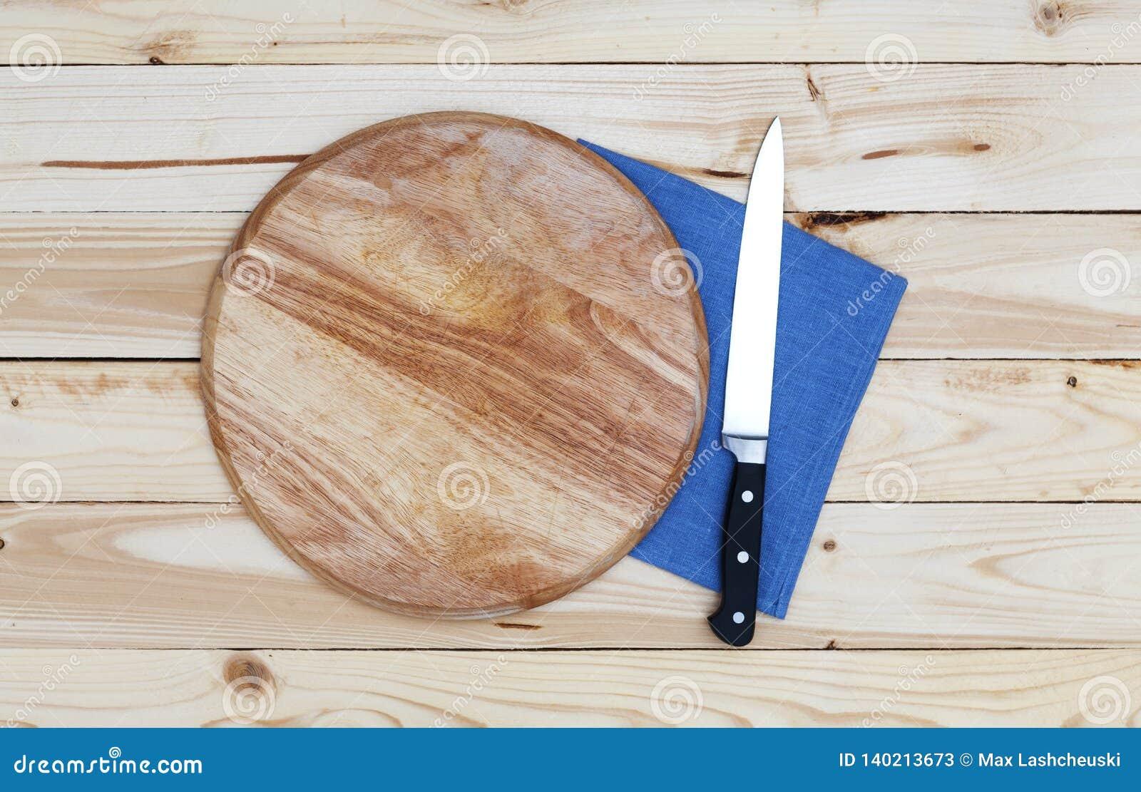 Rund skärbräda med en kniv på en trätabell, bästa sikt