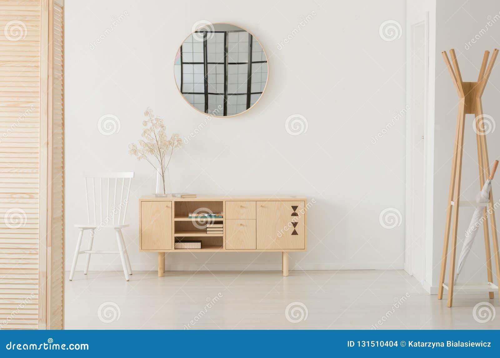 Rund spegel ovanför träkabinettet, verkligt foto med kopieringsutrymme