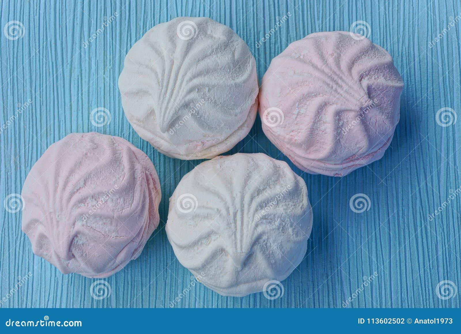 Runda vita rosa marshmallower på en blå tabell