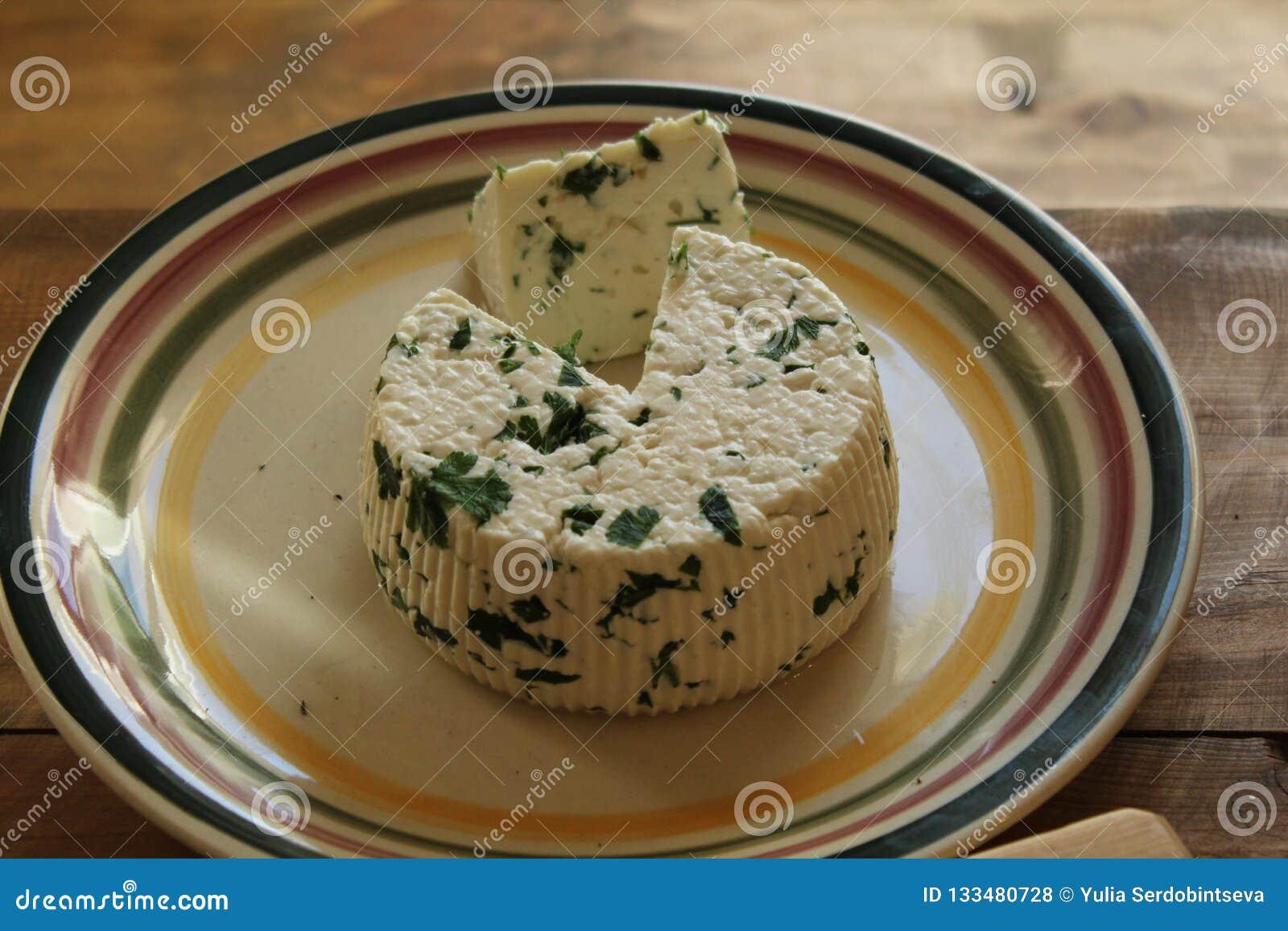 Runder selbst gemachter frischer natürlicher Käse, der auf einer Platte auf einem Holztisch liegt