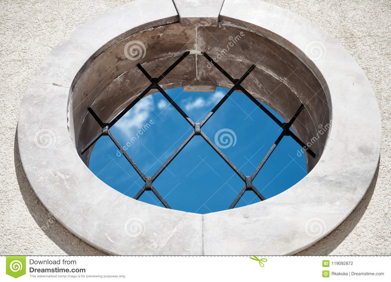 Rundes mittelalterliches Fenster mit Ansicht des blauen Himmels der Stangen - Hintergrund des abstrakten Begriffs - zuhause drauß