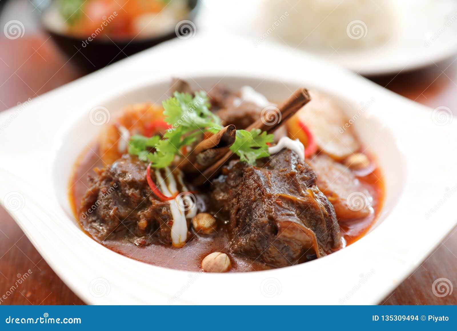 Rundvlees massaman kerrie met rijst en salade op houten lijst, Thais voedsel