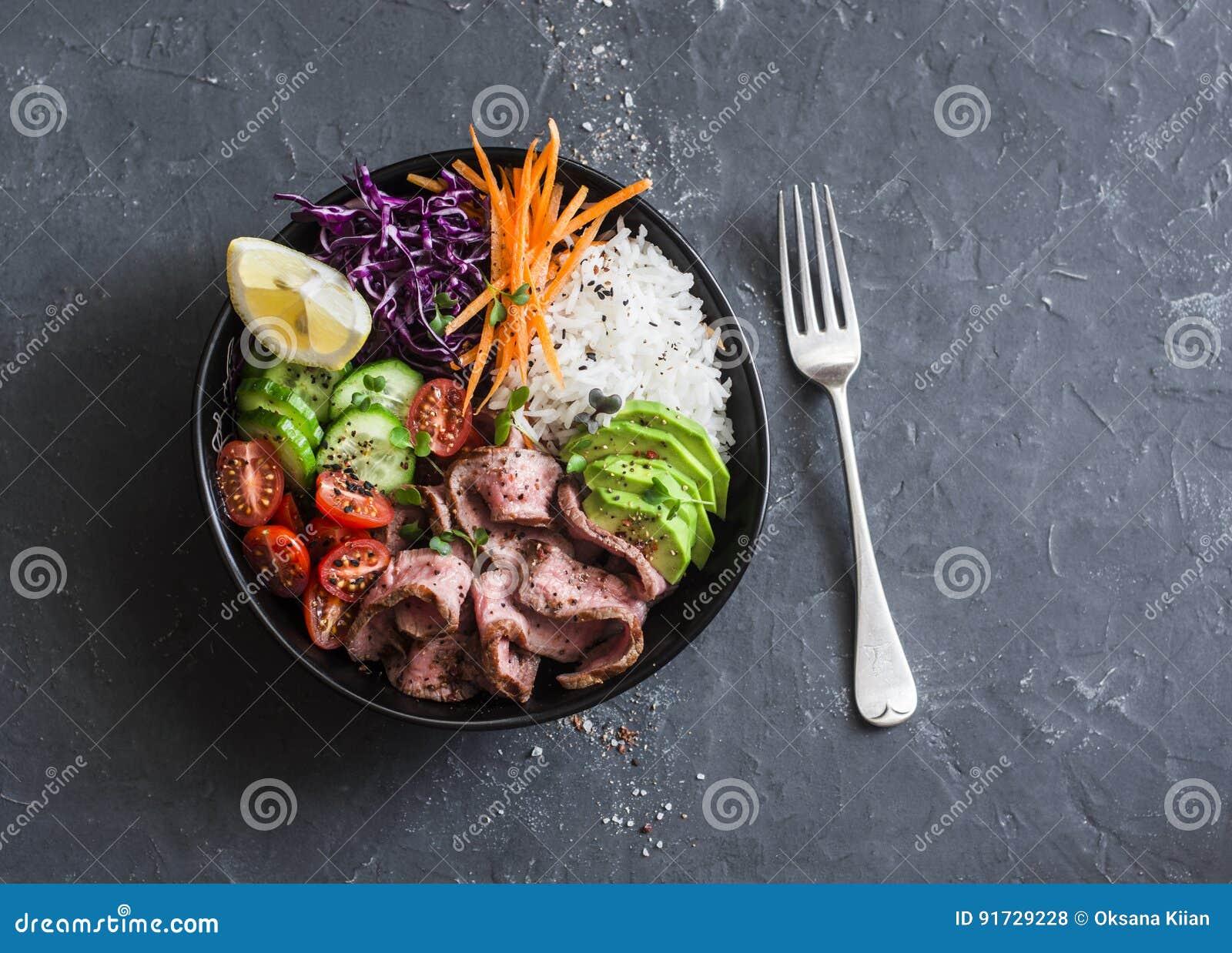 Rundvleeslapje vlees, rijst en plantaardige machtskom Gezond evenwichtig voedselconcept Op een donkere achtergrond