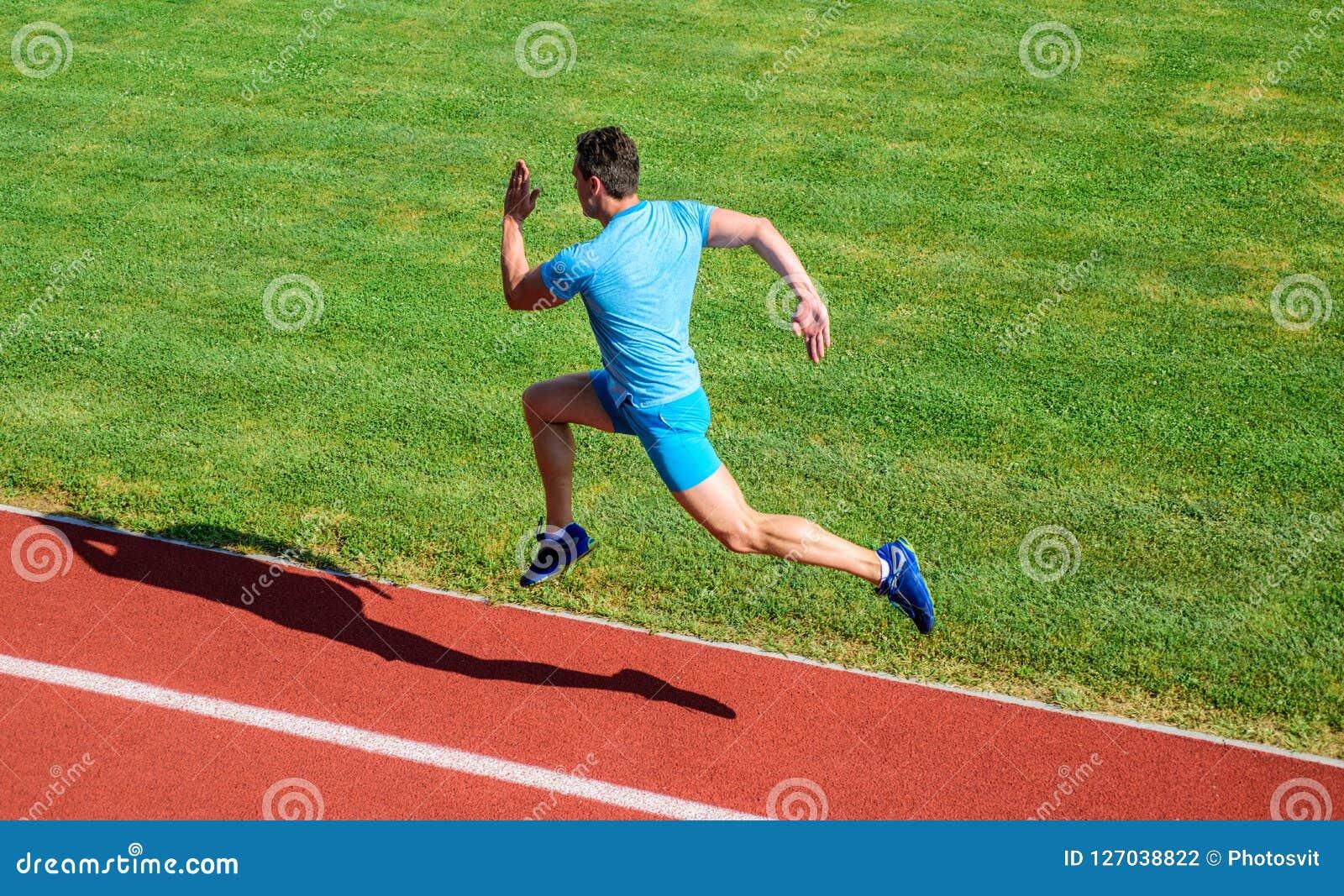 Runner captured in midair. Short distance running challenge. Boost speed. Athlete run track grass background. Run into
