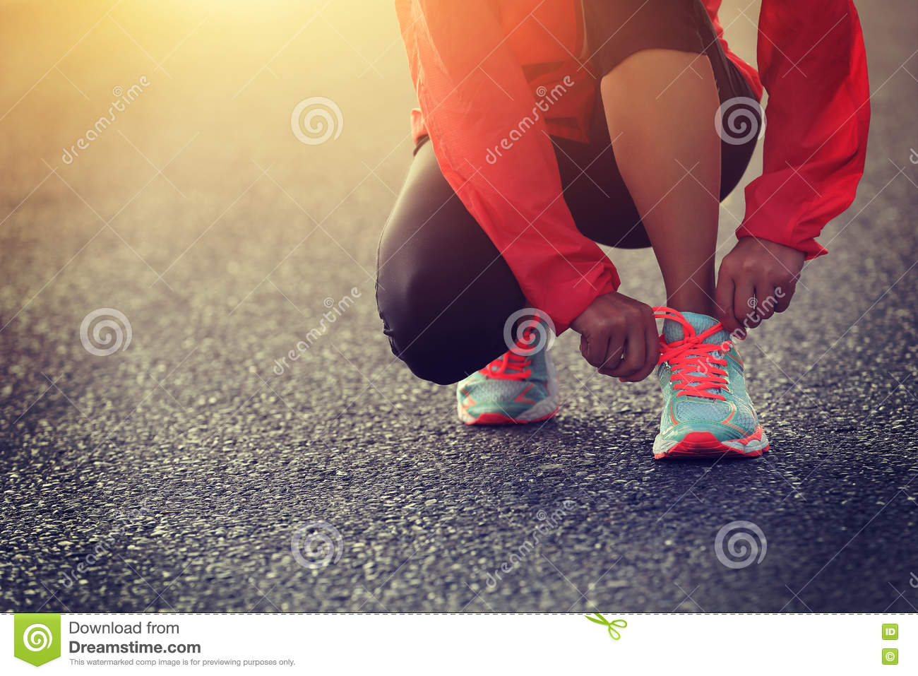 Runner tying shoelace on country road