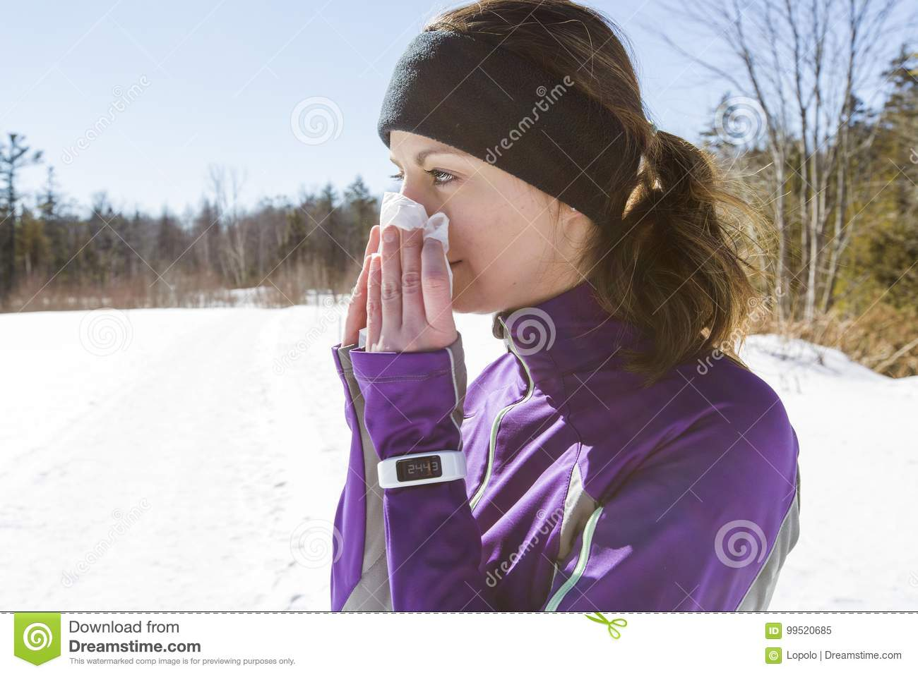 Runner Woman blowing her nose outside in the cold