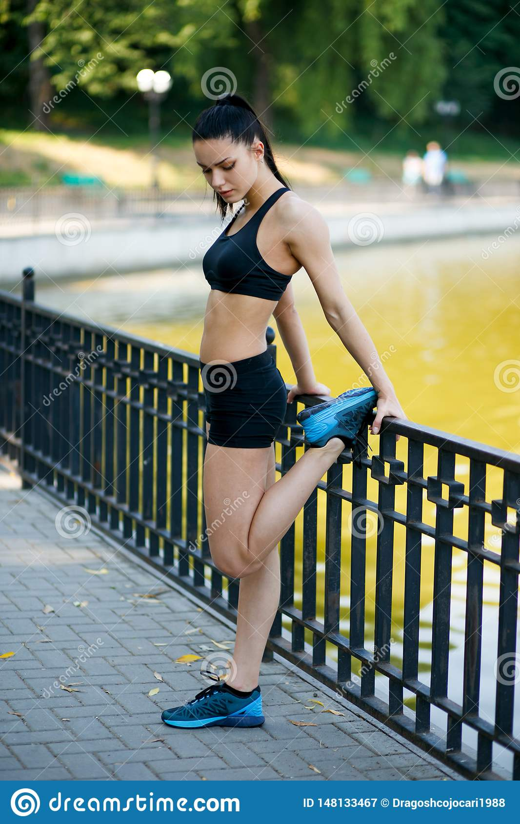 Beautiful fit female fitness girl model doing stretch exercising after workout outside by the lake in the summer time.
