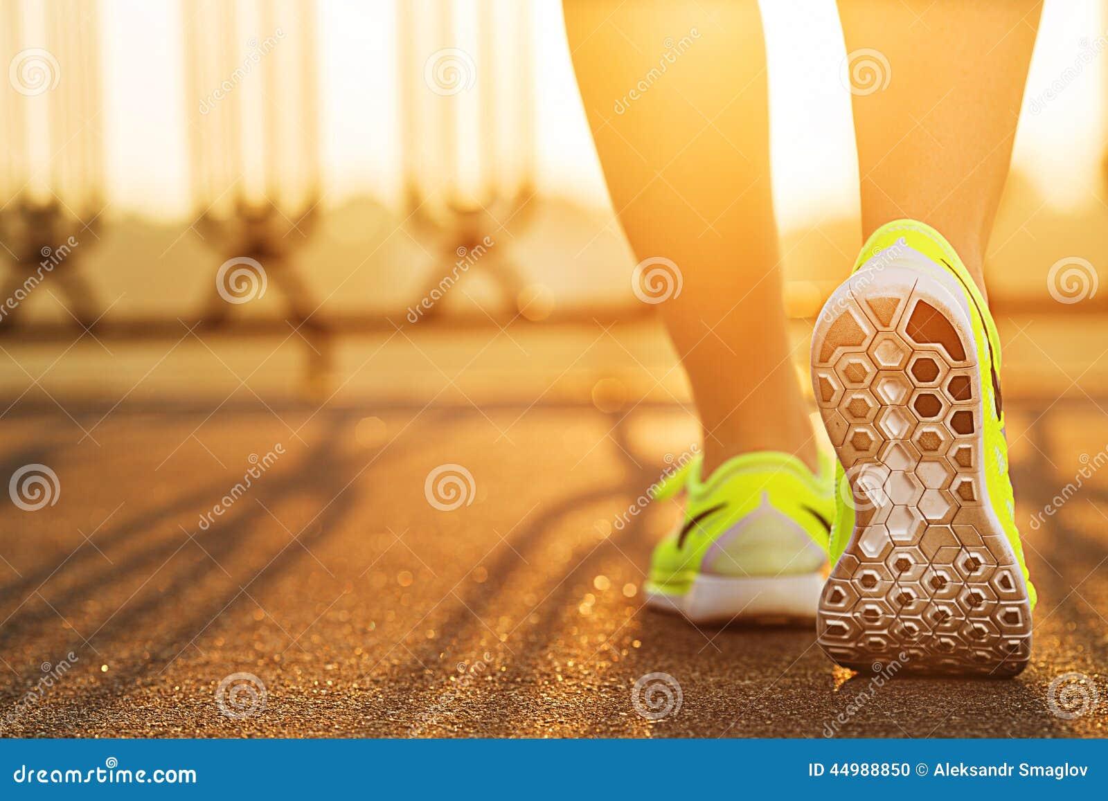 Runner woman feet running on road closeup on shoe. Female fitness model sunrise jog workout. Sports lifestyle concept.