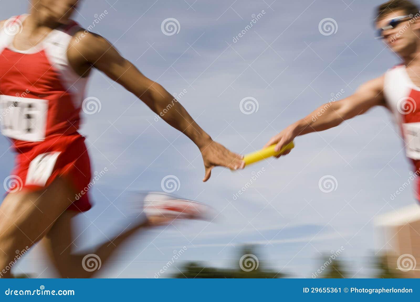 Runners Passing Baton In Relay Race