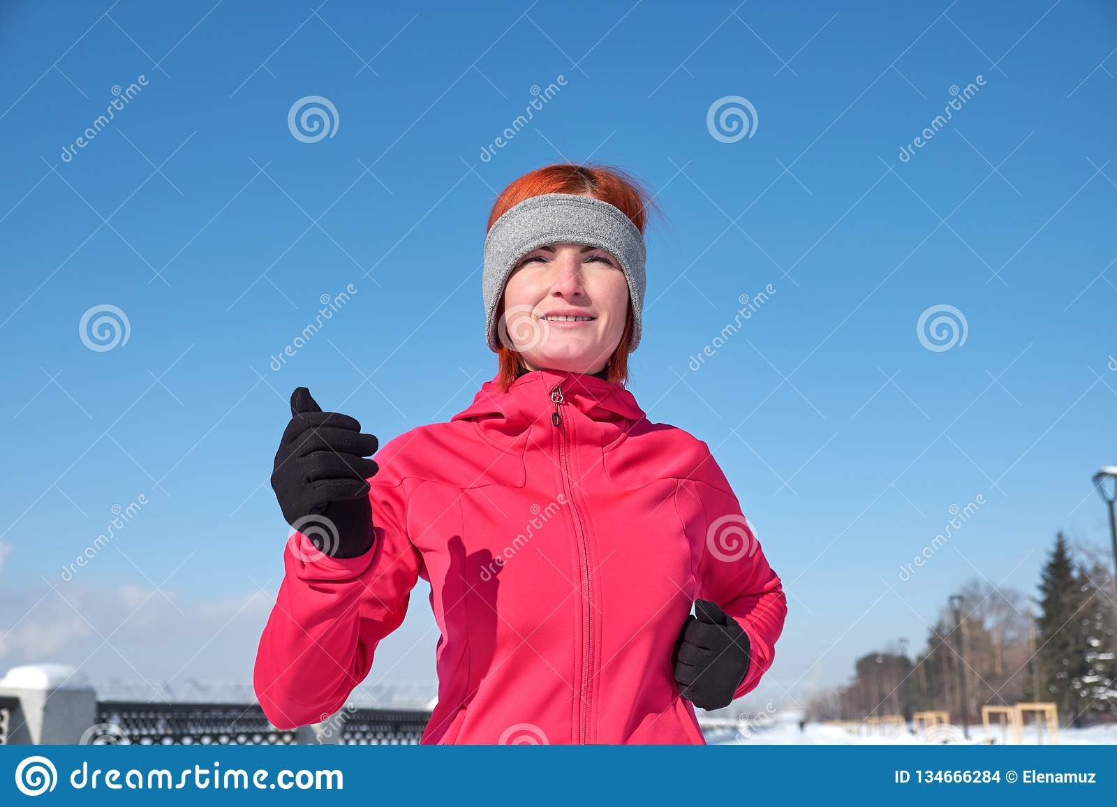 Running athlete woman sprinting during winter training outside in cold snow weather. Close up showing speed and movement