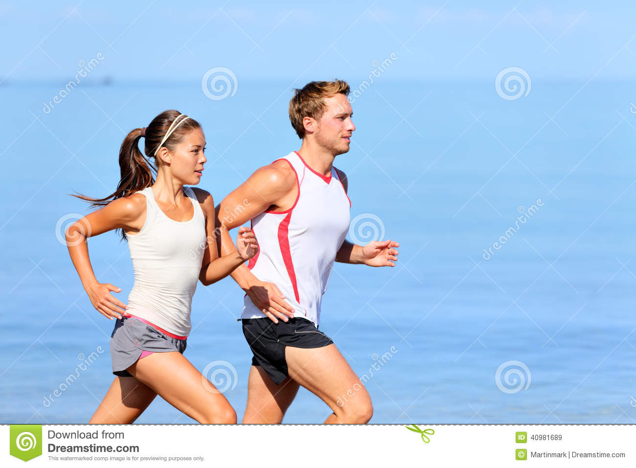 Running couple jogging on beach. Runners training together. Man and ...