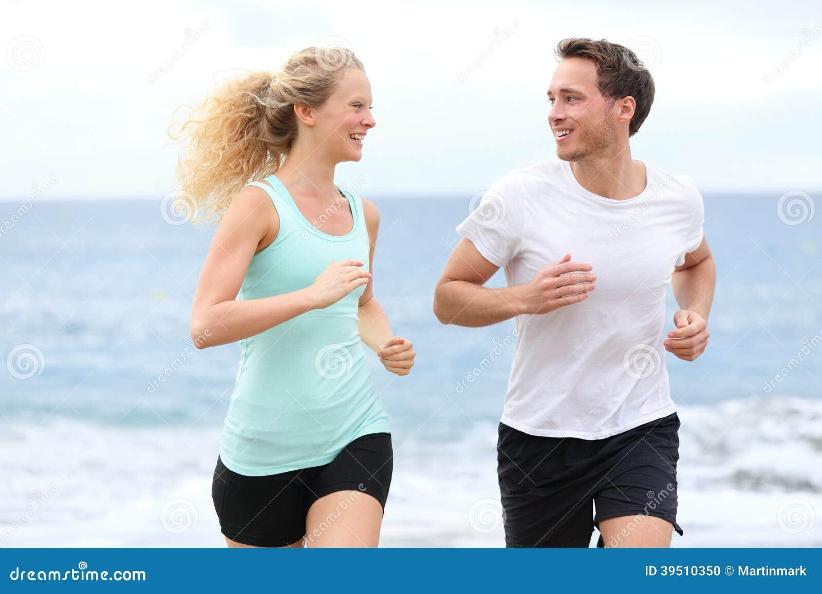 Running couple jogging exercising on beach talking