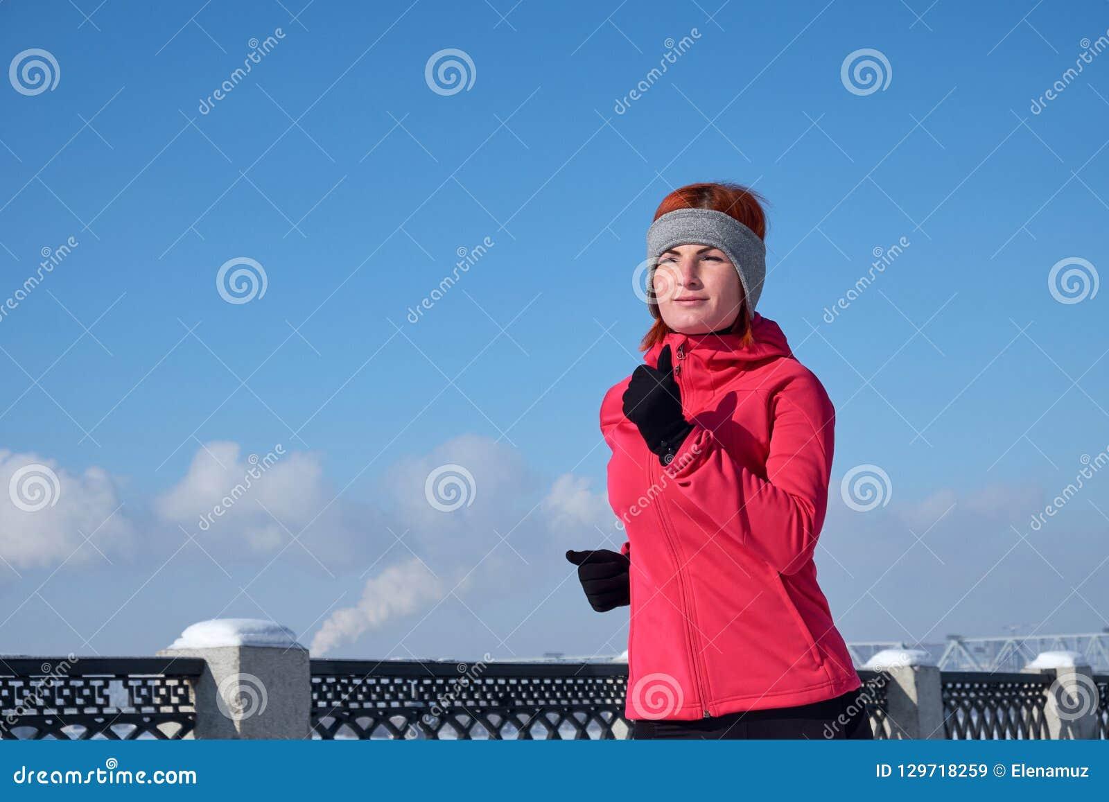Running idrottsman nenkvinna som sprintar under vinterutbildning utanför i kallt snowväder Stäng sig upp uppvisning av hastighet