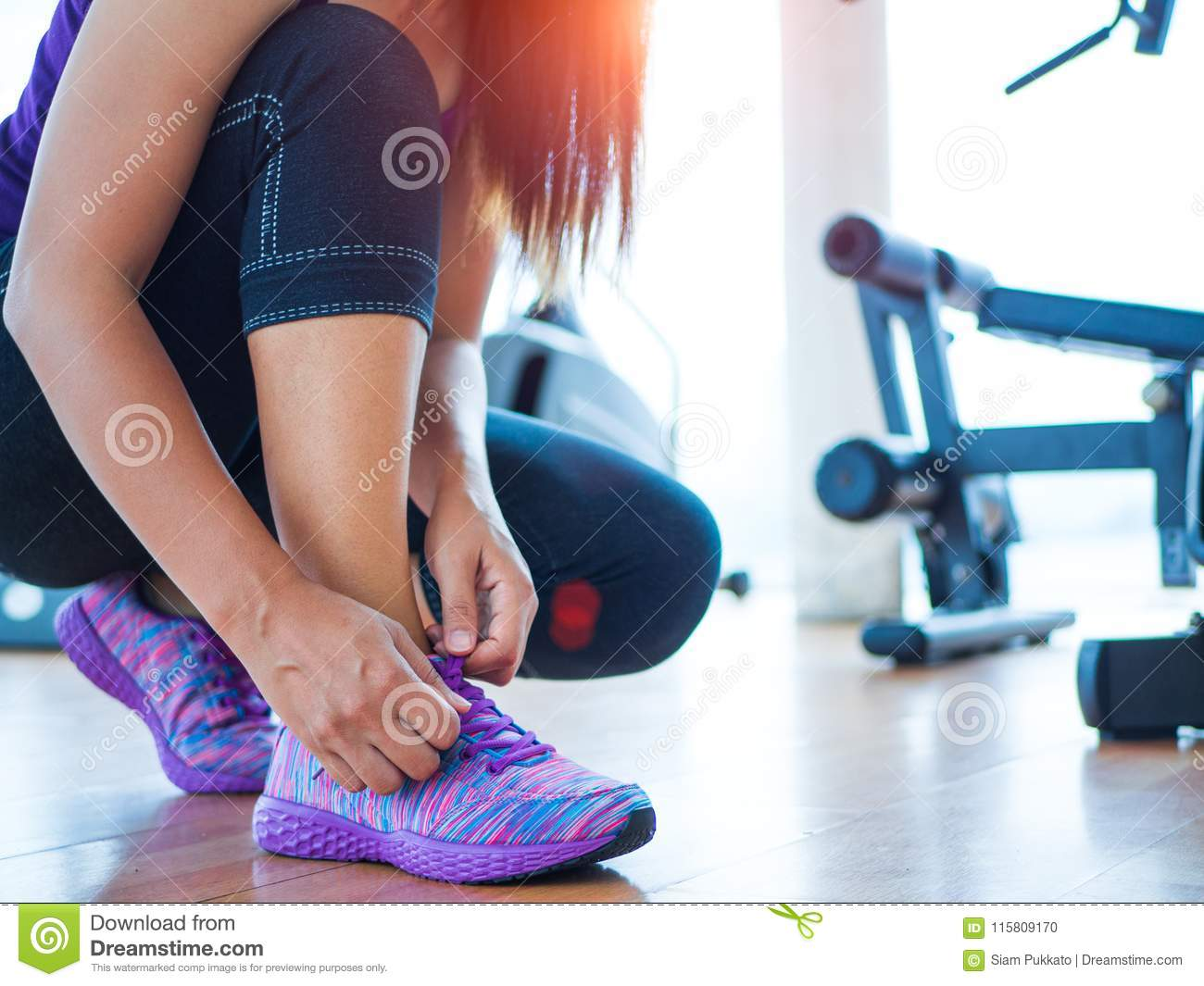 closeup of woman tying shoe laces. Female sport fitness runner getting ready for jogging in gym room