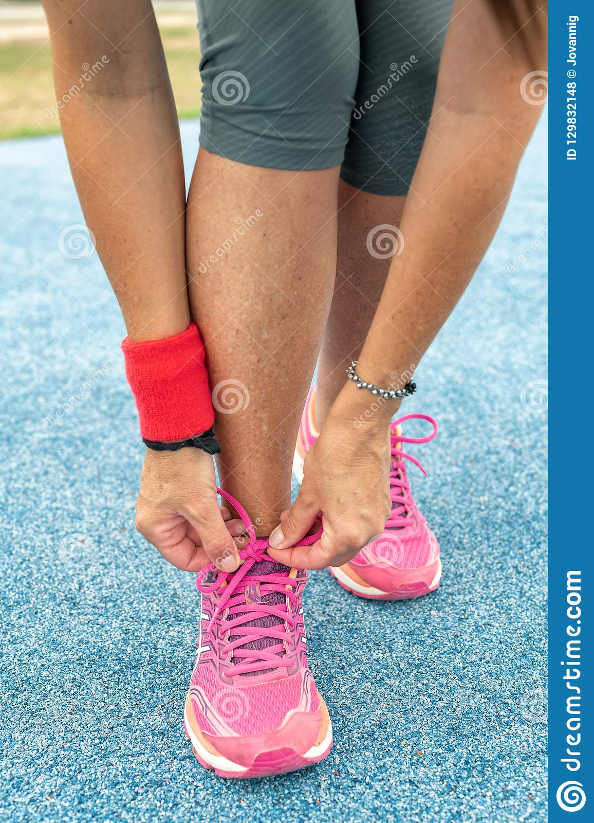 Running shoes - woman tying shoe laces in city park run track