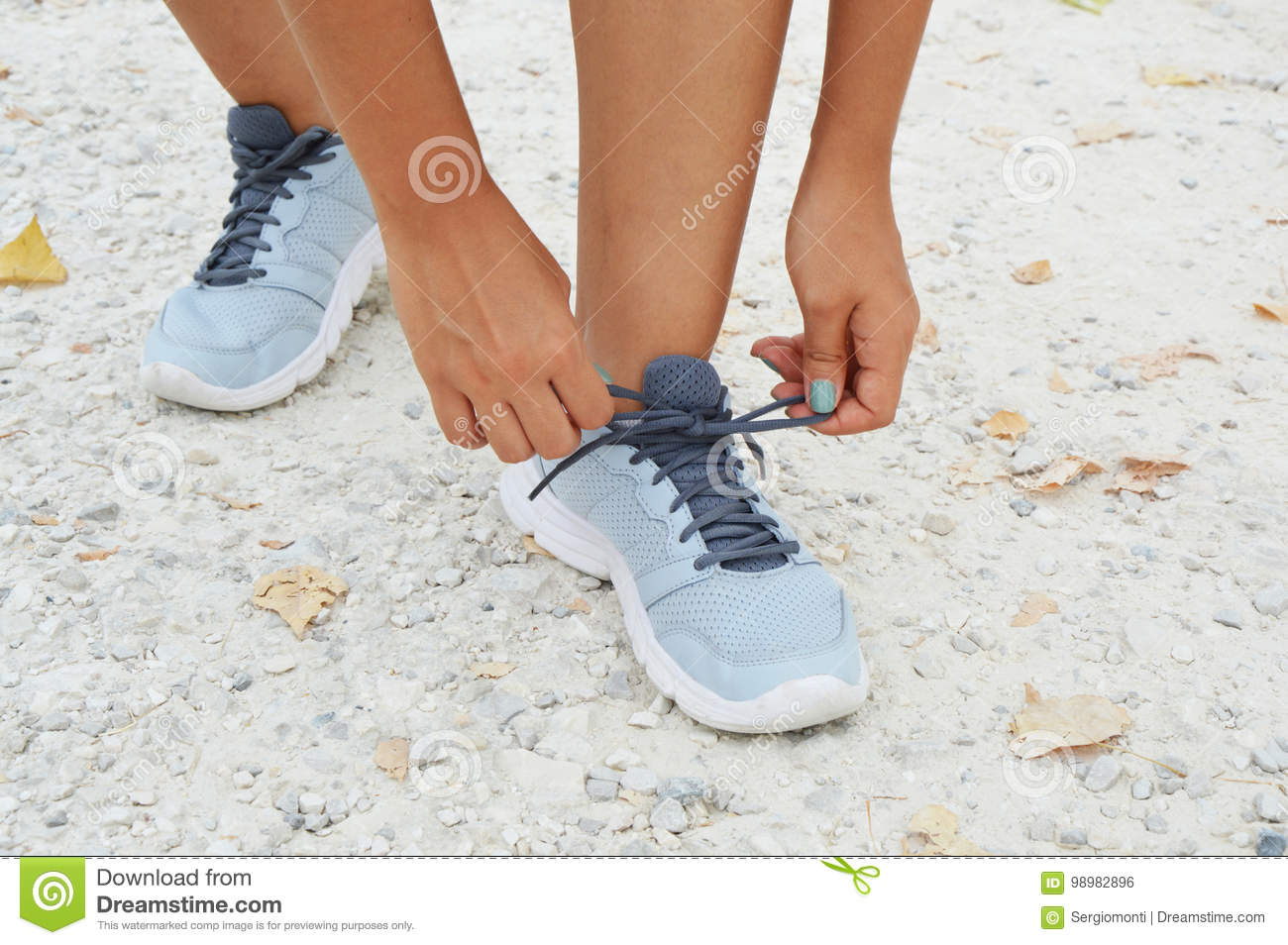 Running shoes. Woman tying shoe laces. Female sport fitness runner getting ready for jogging outdoors on forest path in spring