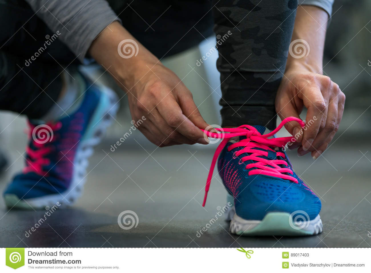 Running shoes - woman tying shoe laces. Woman getting ready for