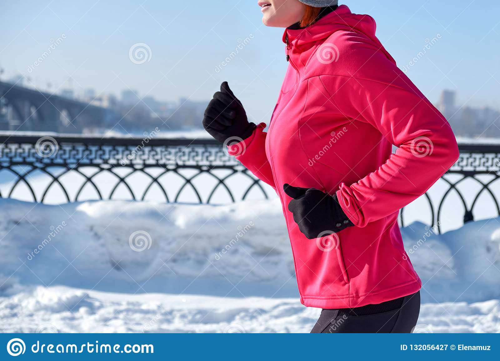 Running sport woman. Female runner jogging in cold winter city wearing warm sporty running clothing and gloves