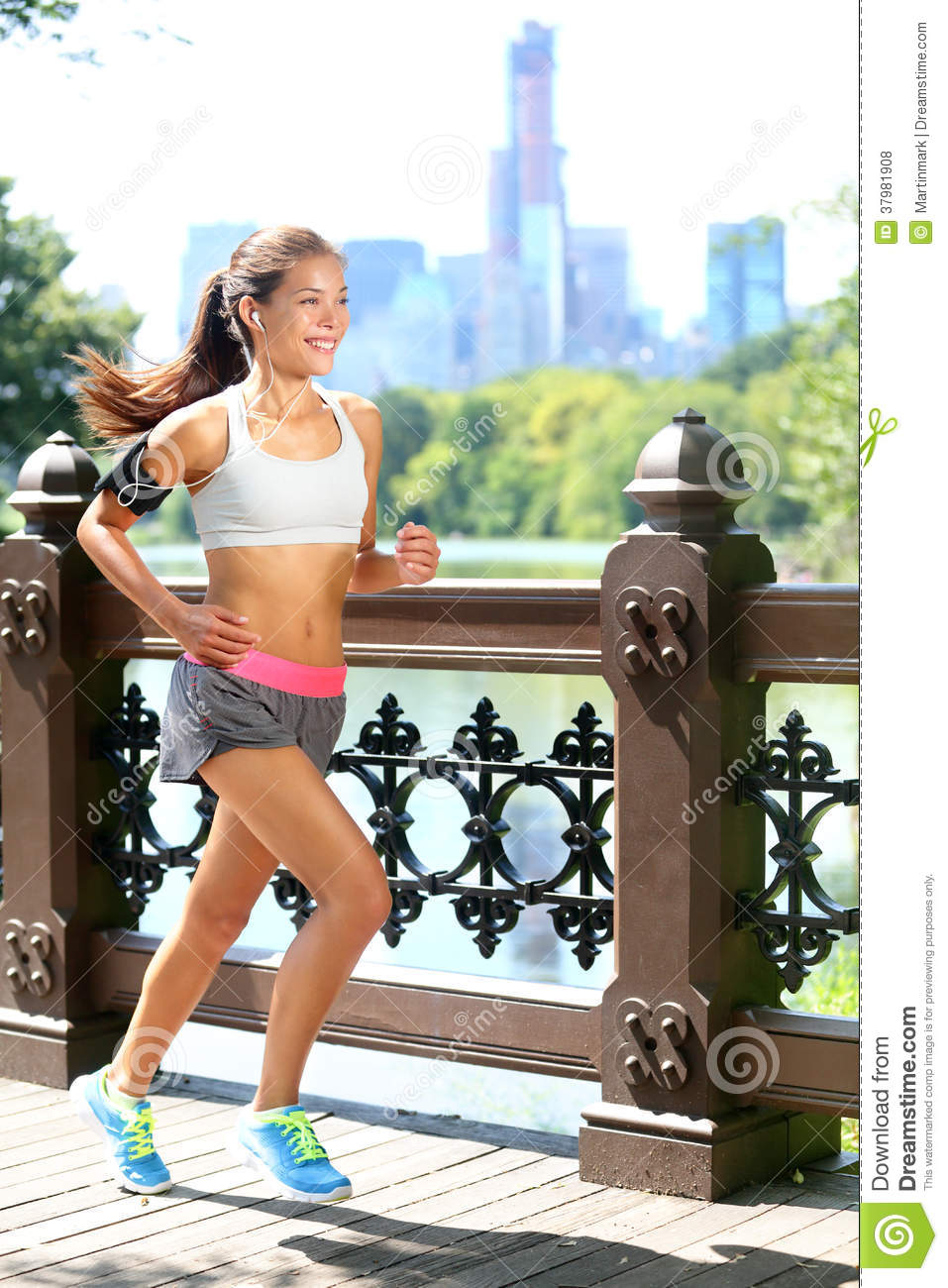 Portrait of beautiful active woman in headset jogging in the wood.