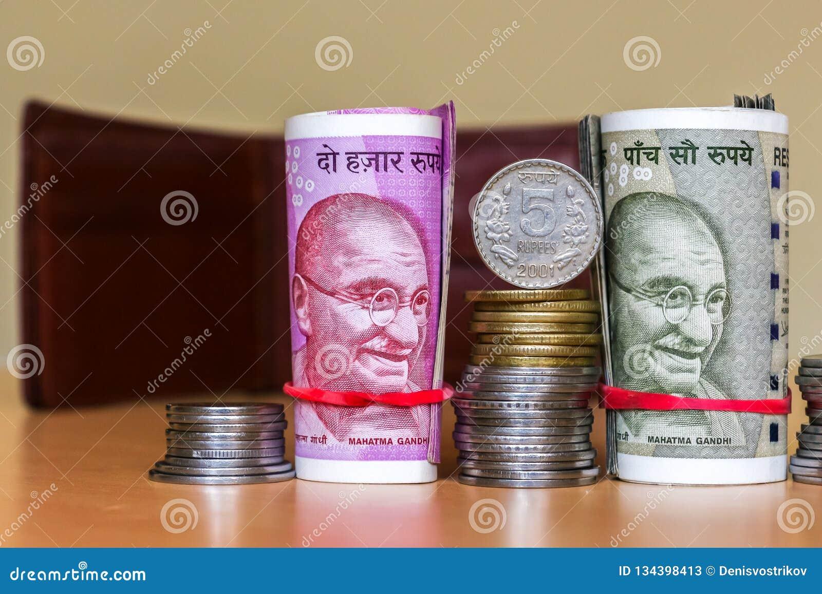 Rupias indias Billetes de banco y monedas empiladas Cartera de cuero en fondo