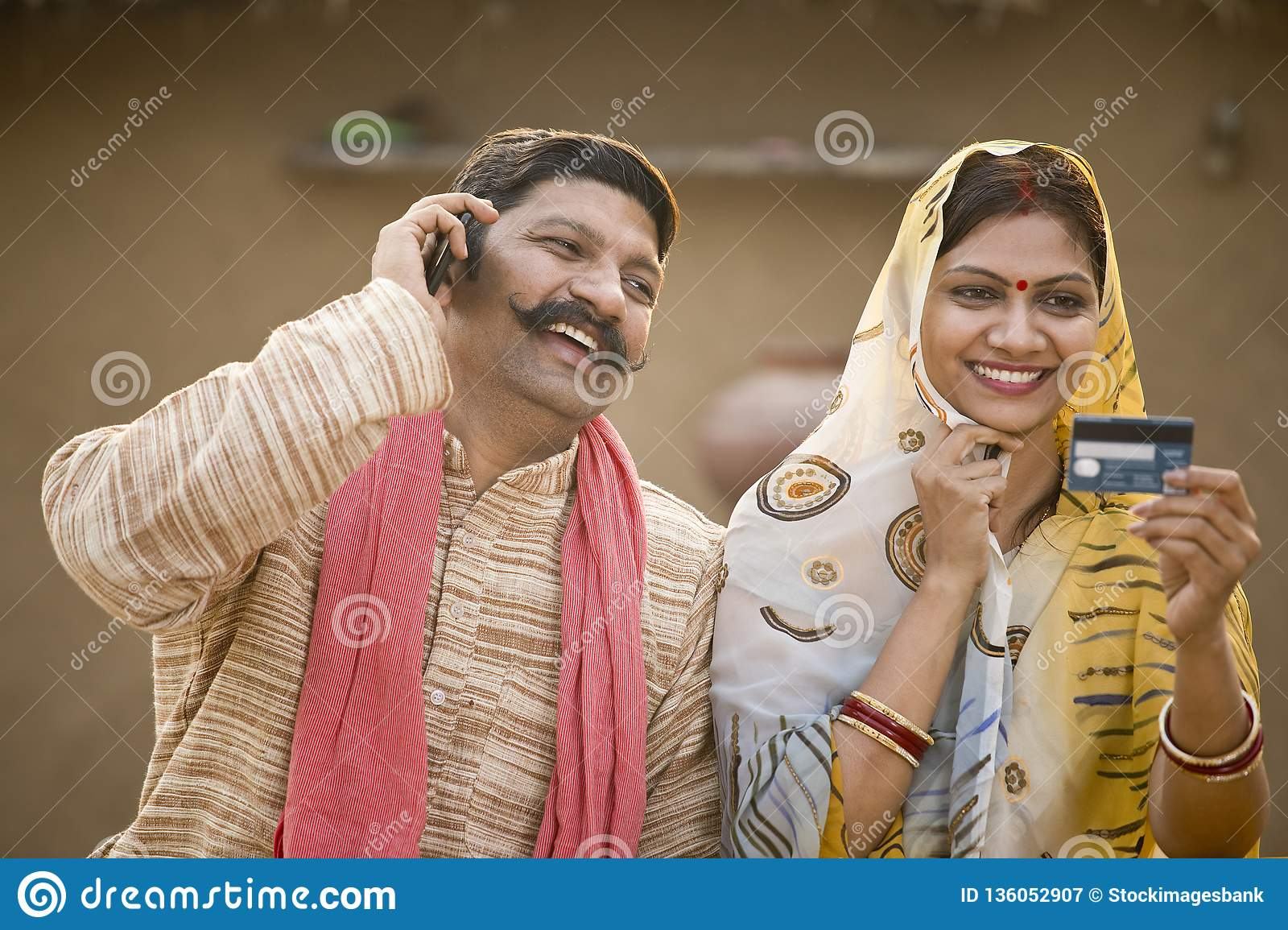 Rural indian couple using credit card and mobile phone at village