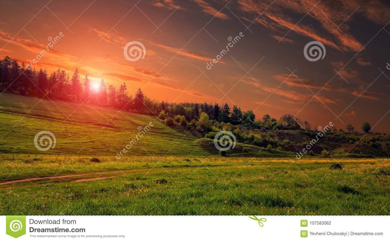 Rural landscape with a hill. Green meadow under sunset, colorful sky with clouds Dramatic morning scene.