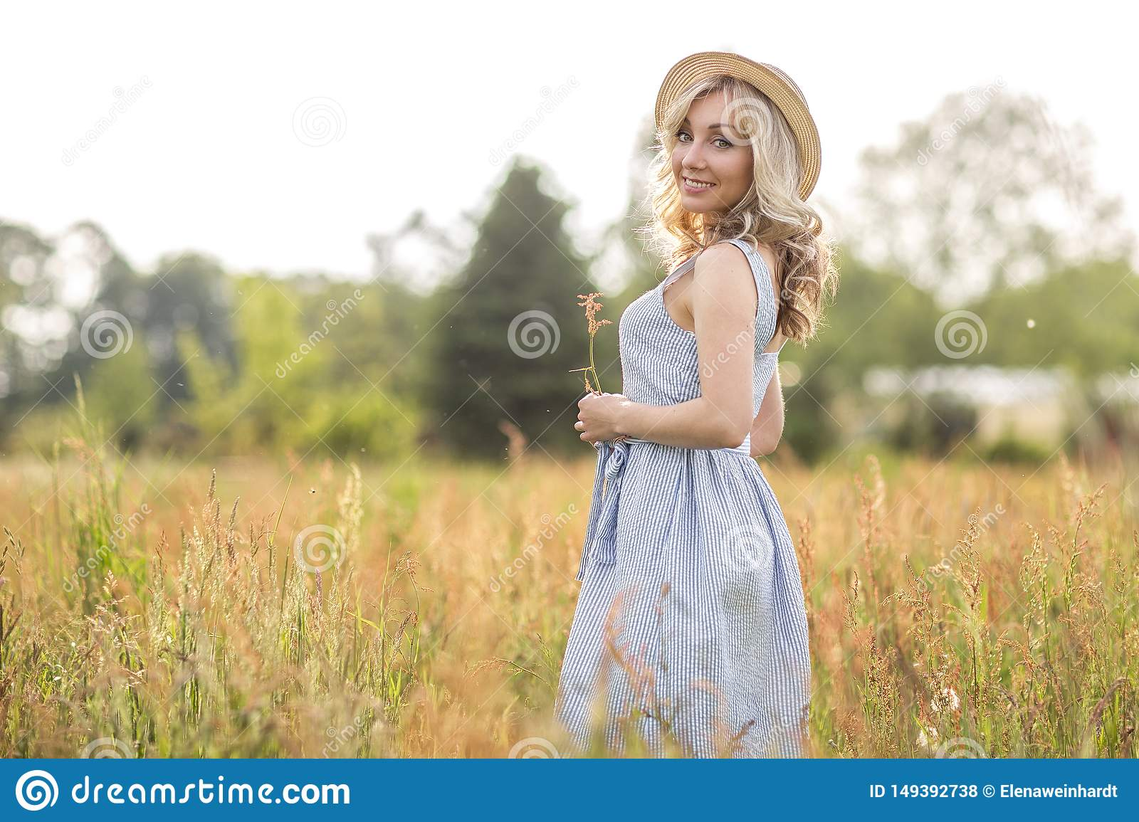 Rural, rural life. Walking through the meadow blonde young woman in a hat. Summertime