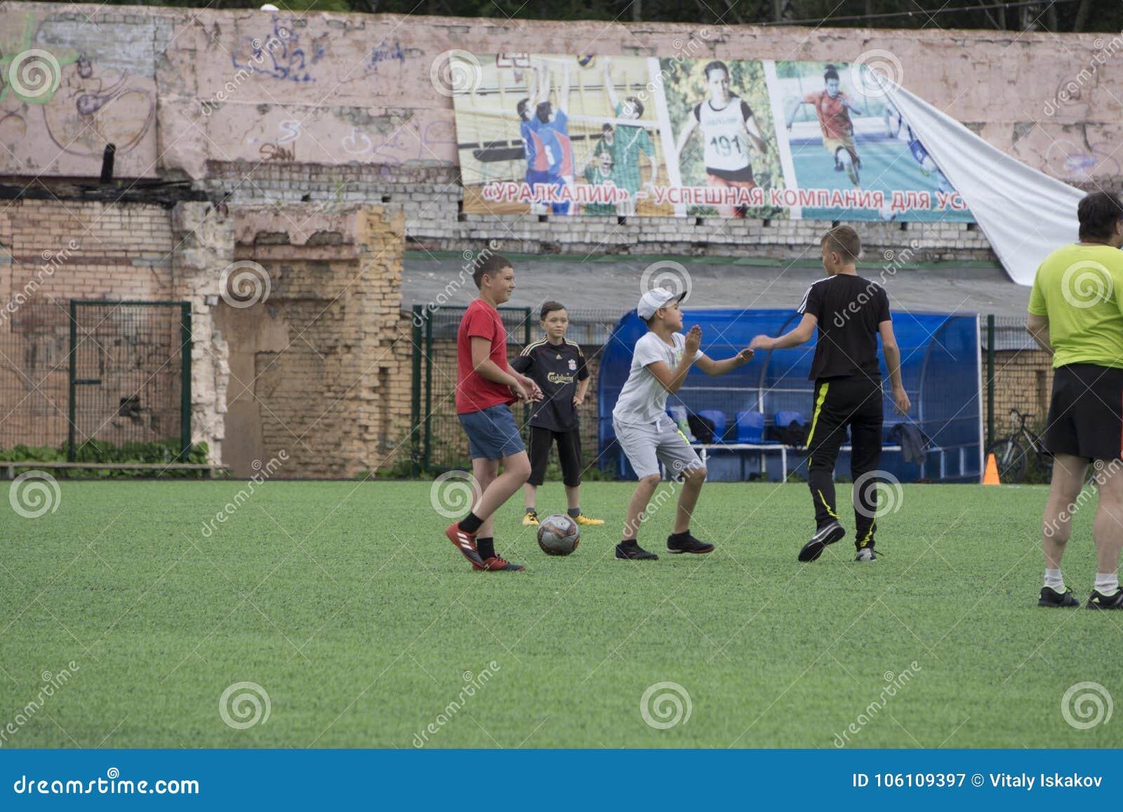 Rusia - Berezniki el 25 de julio de 2017: Los niños pequeños embroman fútbol sala del juego en la zona abierta en la ciudad Junio