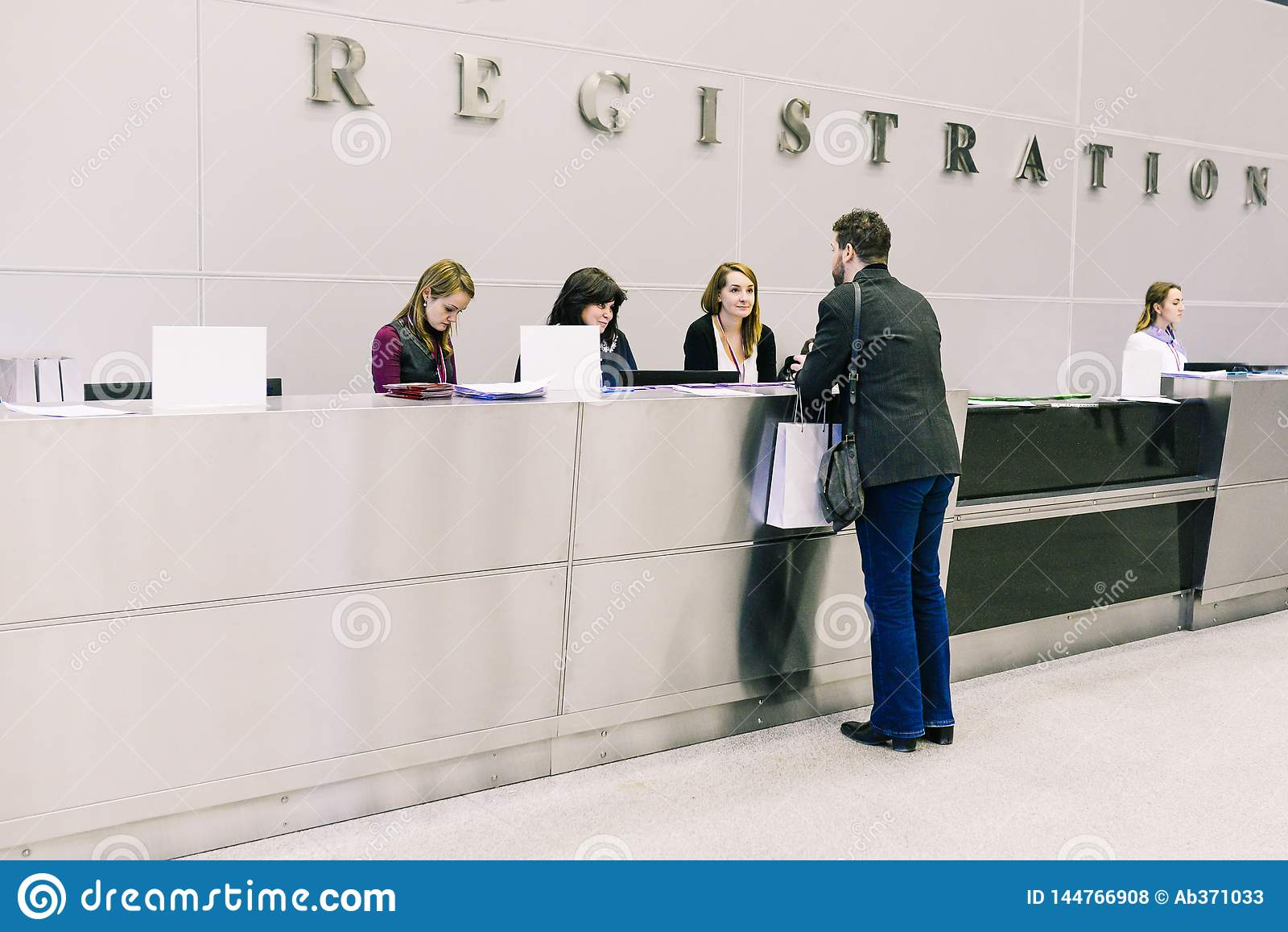 Rusia, ciudad Moscú - 18 de diciembre de 2017: El hombre en el mostrador o en el hotel, la oficina o el aeropuerto Las muchachas
