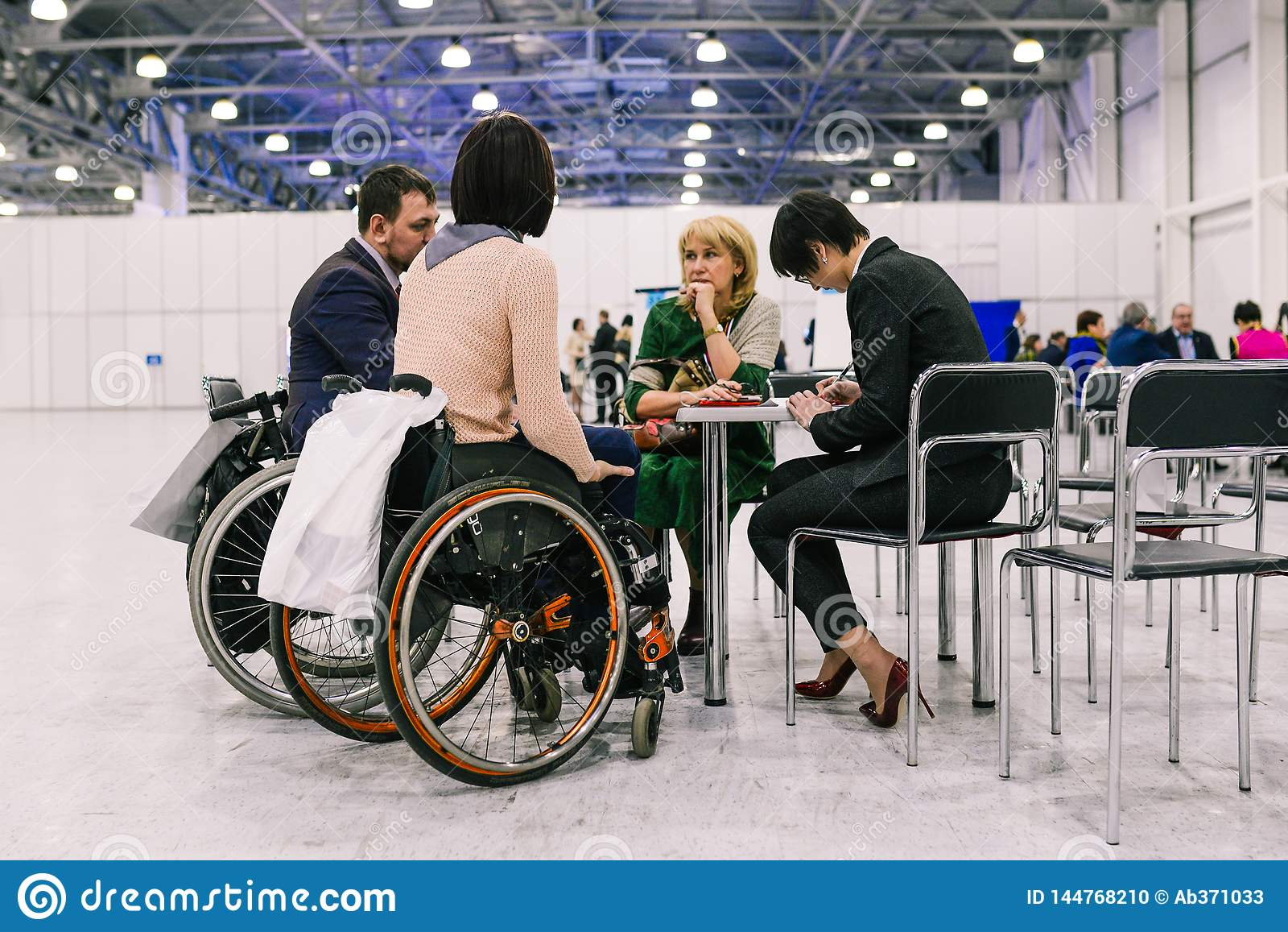 Rusia, ciudad Moscú - 18 de diciembre de 2017: Mujer joven en una silla de ruedas Un grupo de personas que discute un proyecto e