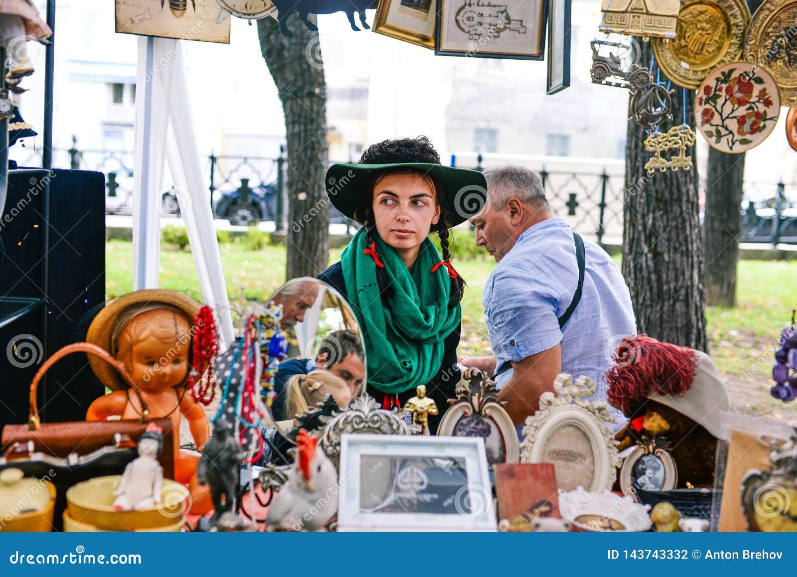 Rusia, ciudad Moscú - 6 de septiembre de 2014: Muchacha hermosa joven en un sombrero con paly y bufanda verde Una mujer vende ant